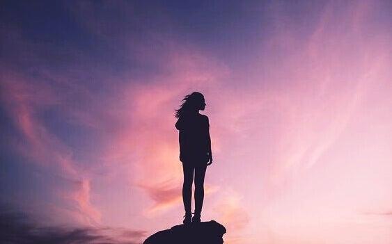 nainen seisoo kalliolla