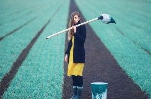 nainen maalaa peltoa