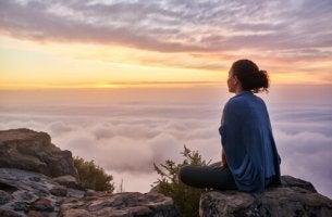nainen meditoi pilvien yläpuolella