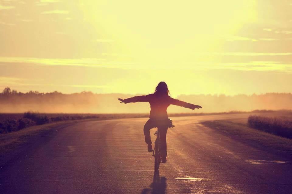 nainen ajaa pyörällä ilman käsiä
