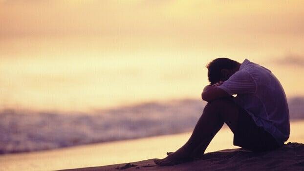 surullinen mies rannalla