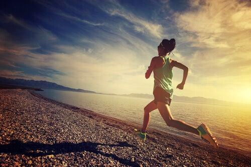 nainen juoksee kivisellä rannalla