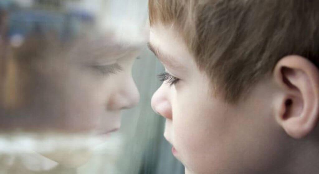 poika katsoo ikkunasta ulos