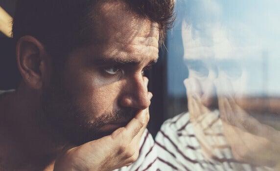 surullinen mies katsoo ulos ikkunasta