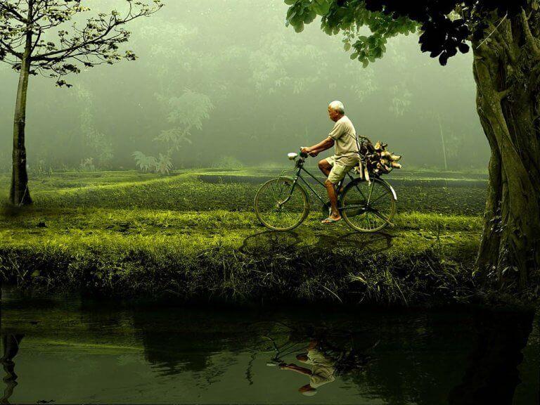 vanha mies pyöräilee joen varrella