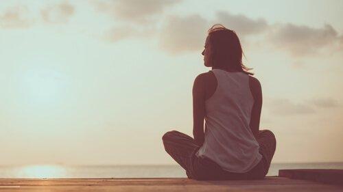nainen istuu rannalla ja katsoo merelle