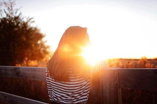 nainen katselee ilta-aurinkoa