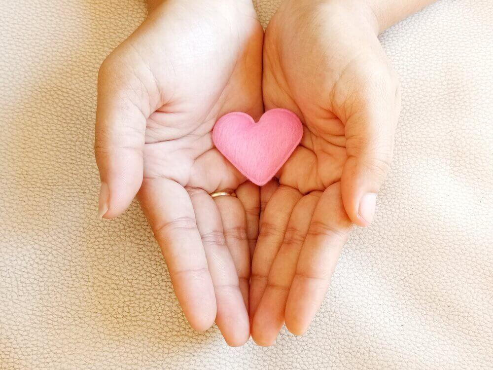 pieni vaaleanpunainen sydän kämmenellä