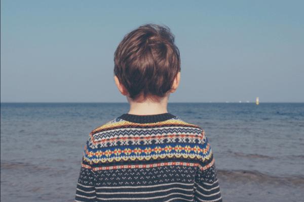 yksinäinen poika katsoo kauas merelle