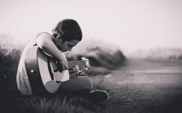 poika soittaa kitaraa
