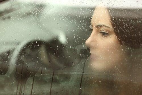 nainen autossa kun ulkona sataa