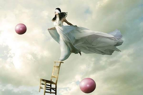 nainen tasapainottelee tuolin päällä taivaalla