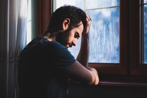 surullinen mies ikkunan edessä