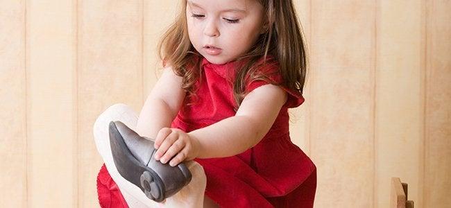 pikkutyttö laittaa kenkää jalkaan