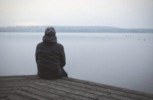 yksinäinen mies katsoo järvelle