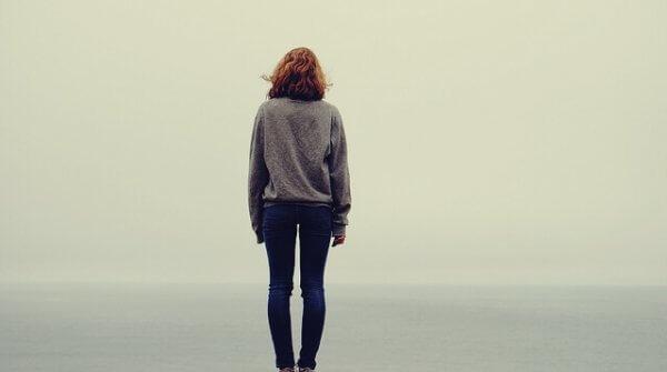 yksinäinen nainen katsoo merelle