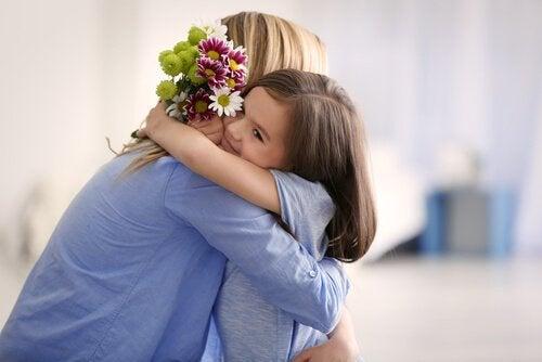 äiti ja pikkutyttö halaavat