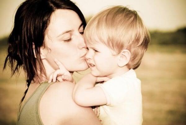 äiti suukottaa pientä poikaansa