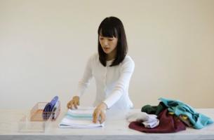 Marie Kondo järjestämässä vaatteita