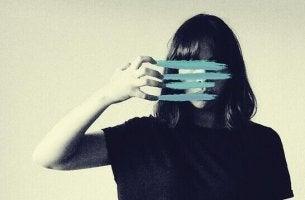nainen viivaa kynsillään yli kasvojensa