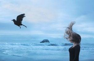 nainen ja varis rannalla