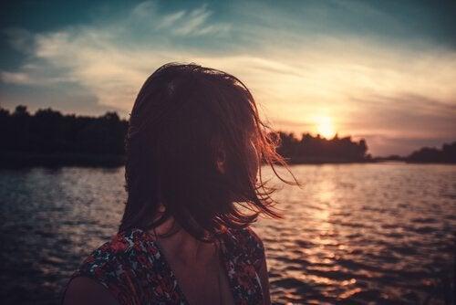 nainen katsoo järvelle ilta-aurinkoon