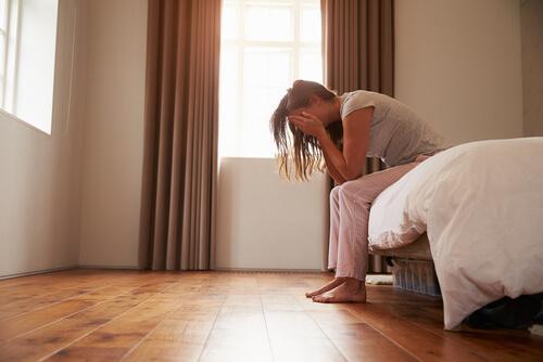 nainen istuu epätoivoisena sängyllä