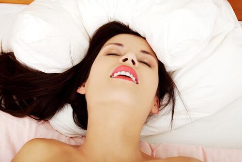 nainen nauttii sängyssä