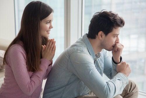 nainen rukoilee miehen selän takana