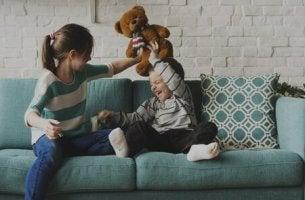 sisarukset leikkivät sohvalla