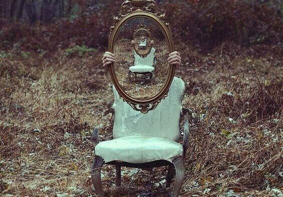 ihminen tuolin takana pitelee peiliä