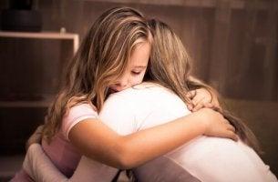 tyttö ja äiti halaavat