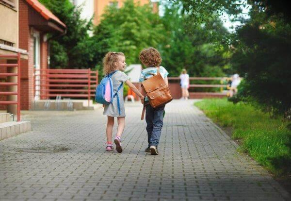 kaksi lasta menee yhdessä kouluun