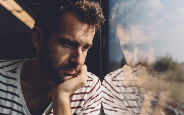 mies katsoo surullisena junan ikkunasta ulos