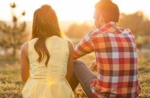 nainen ja mies istuvat ulkona juttelemassa