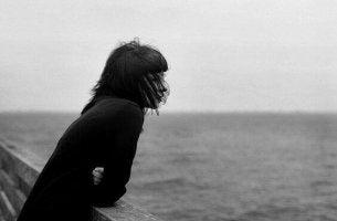 yksinäinen nainen katselee merelle