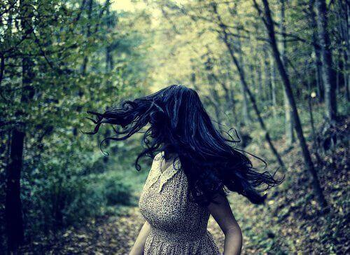nainen katsoo taakseen metsäpolulla