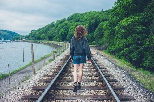 tyttö kävelee junanraiteilla