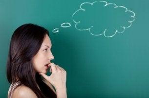 nainen ja liitutauluun piirretty ajatuskupla