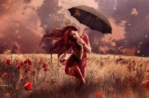 nainen pellolla sateenvarjo mukanaan