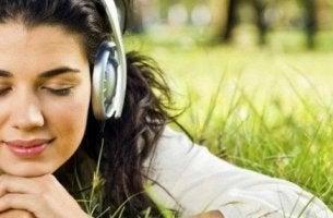 nainen kuuntelee musiikkia nurmikolla