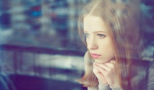 nainen katsoo ikkunasta ulos