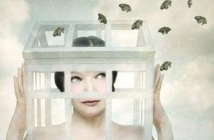 naisen pää häkissä ja sieltä lentää perhosia