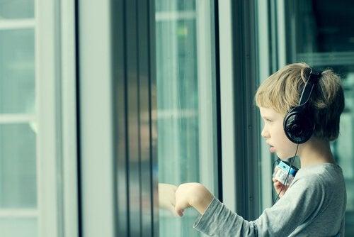 poika kuuntelee musiikkia ja katsoo ulos ikkunasta