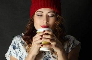 nainen juo teetä tai kahvia pipo päässä
