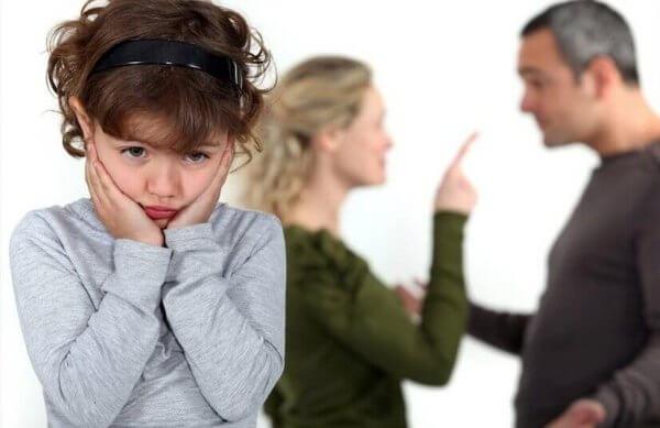 pikkutyttö ja takana riitelevät vanhemmat