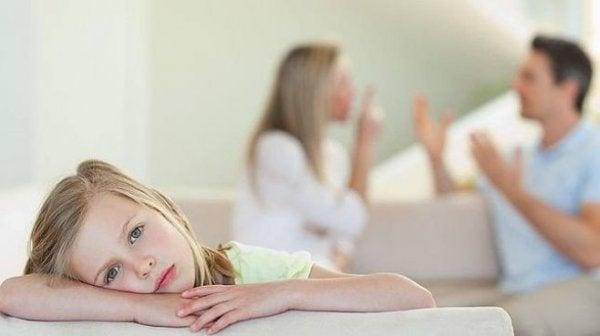 surullinen tyttö kuuntelee kun vanhemmat riitelevät
