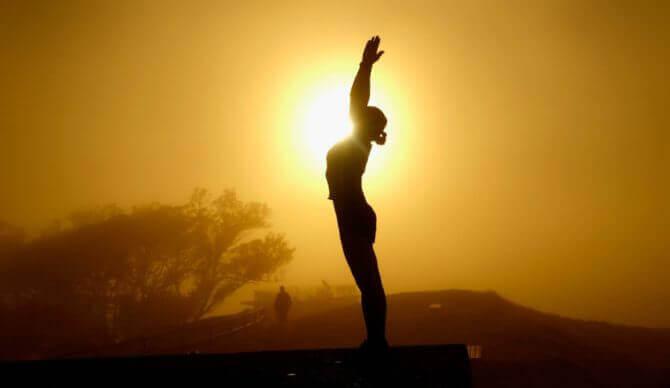 nainen harrastaa taijita auringonlaskussa