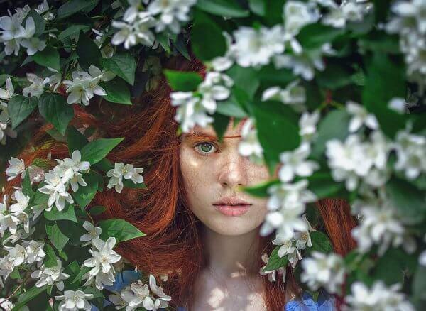 nainen kukkivan puun lomassa