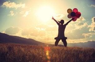 nainen hyppii pellolla ilmapallojen kanssa